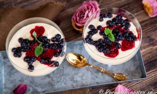 Vit chokladcrème i coupe champagneglas garnerade med blåbär och hallon