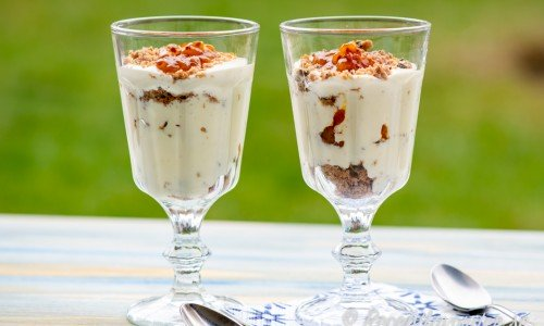 Vit chokladmousse varvat med hjortron och smulad kakor - kakcrunch - serverat i glas.
