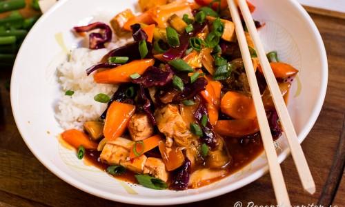 Wokad tofu och grönsaker i sötsur sås med ris på tallrik