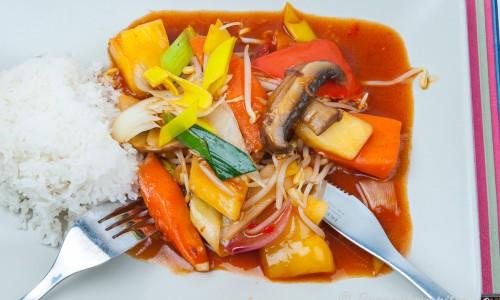 Wokade grönsaker i sötsur sås med ris på tallrik
