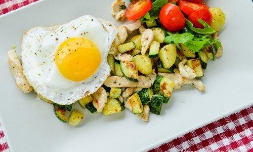 Zucchinipytt med kyckling, lök och kokt potatis serverad med stekt ägg och en tomat- och grönsallad.