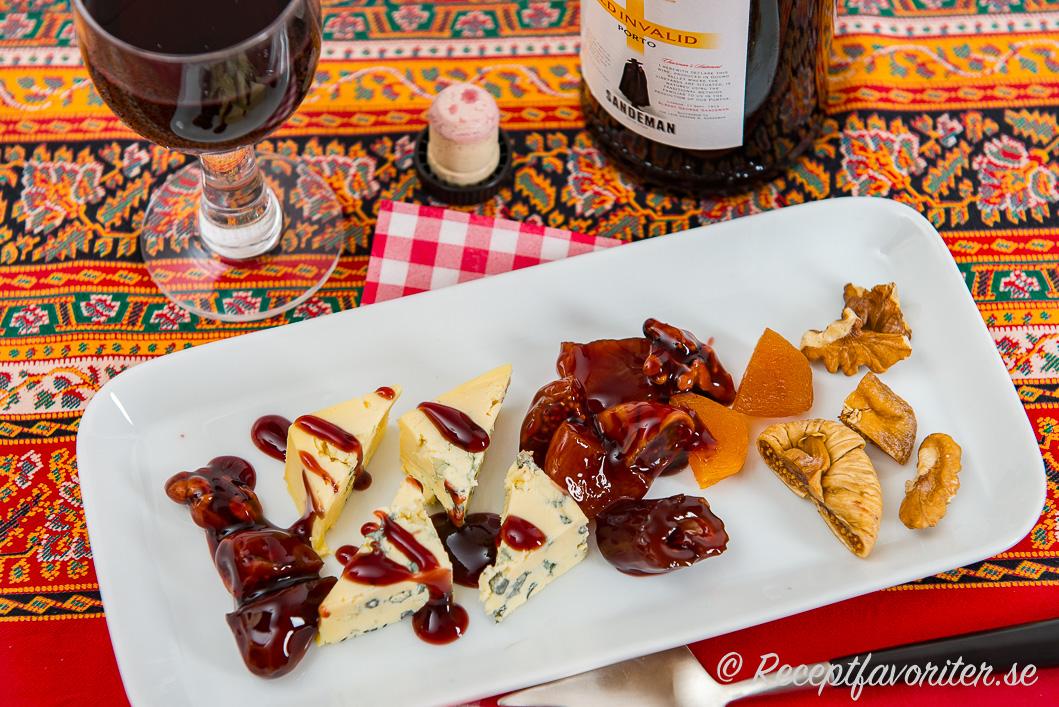 En ostdessert av ädelost, en söt sås/sirap med portvin, nötter och torkad frukt på tallrik med ett glas fruktigt Ruby portvin.