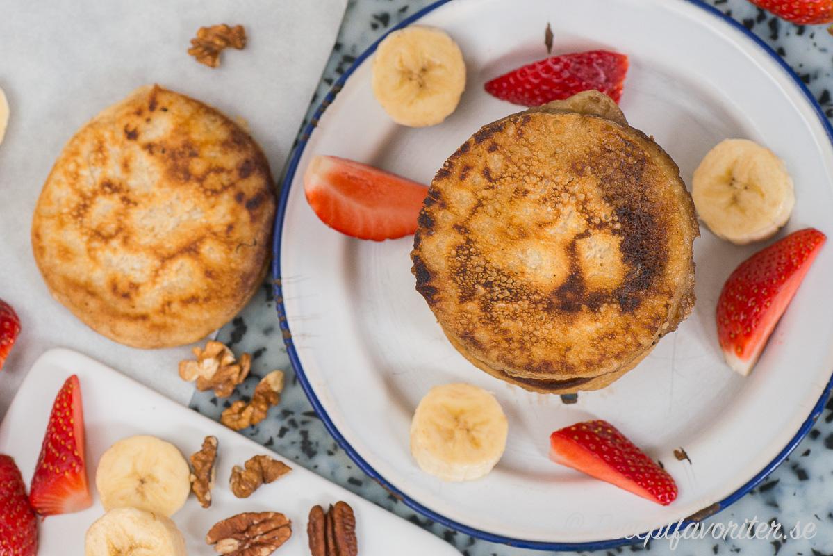 Fluffiga veganska pannkakor i amerikansk stil serverad med frukt, bär och nötter.
