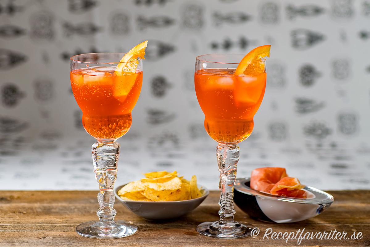 Två glas Aperol Spritz garnerade med apelsin och serverade med chips och parmaskinka.
