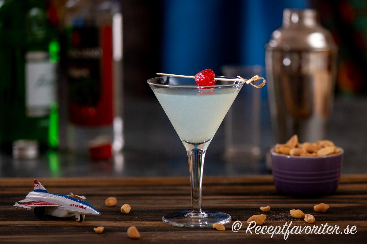Aviation cocktail serverad i martiniglas med jordnötter vid sidan.