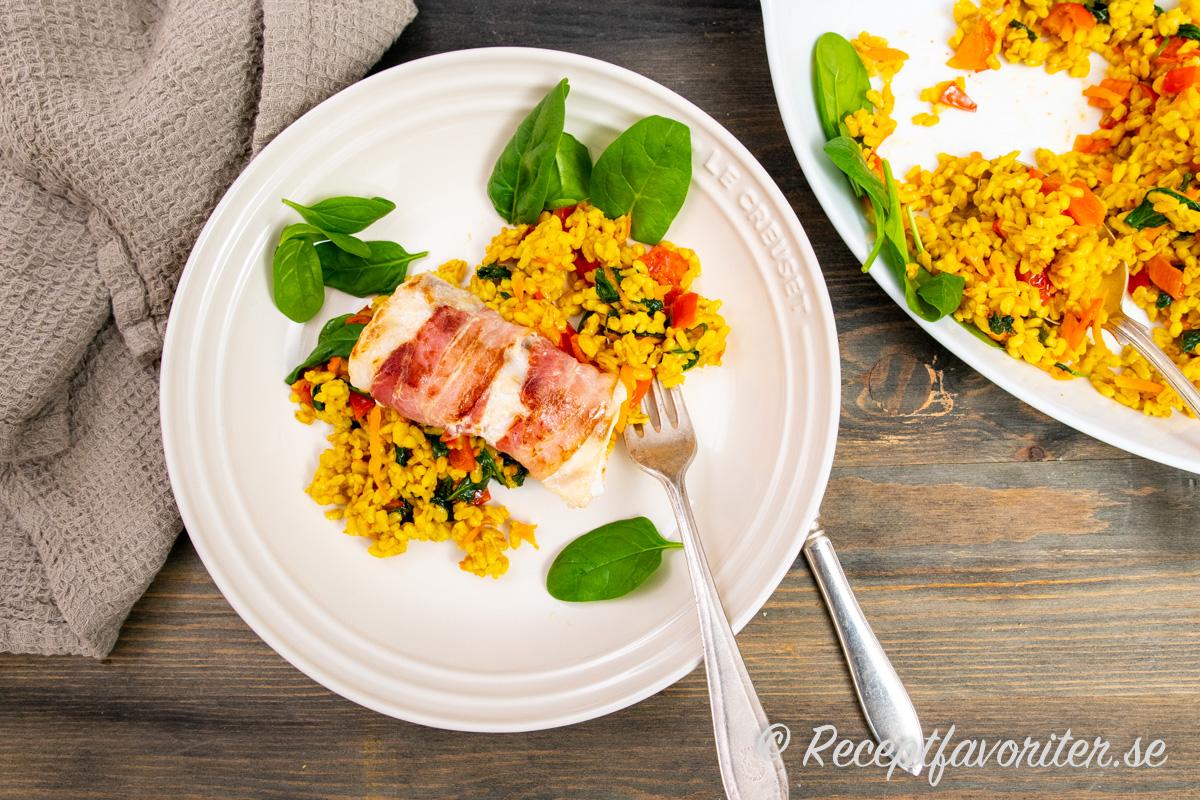 Torskryggen lindad i bacon serverad med en matig sallad med havreris och grönsaker.