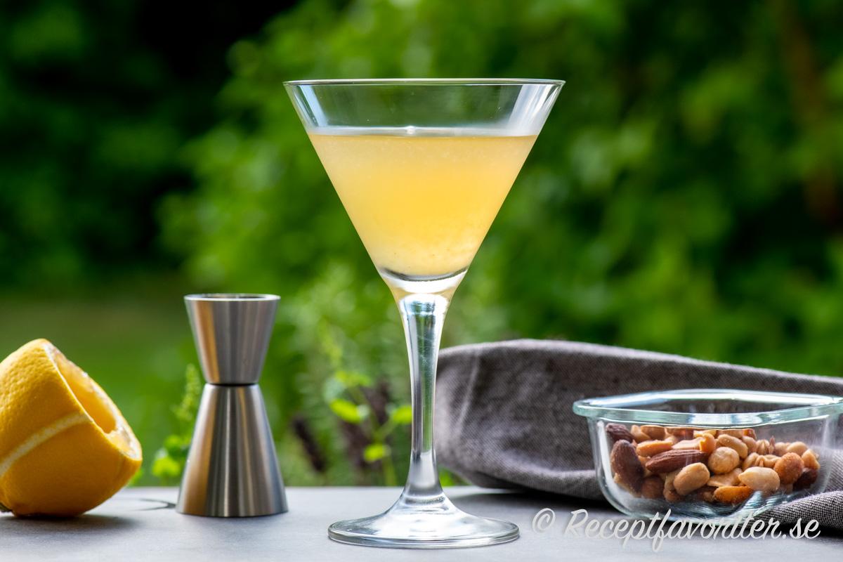 Between the Sheets cocktail i martiniglas serverad med nötter.