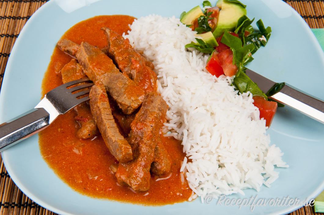 Stroganoff lagad med mört biffkött serverat på tallrik med kokt ris och grönsallad