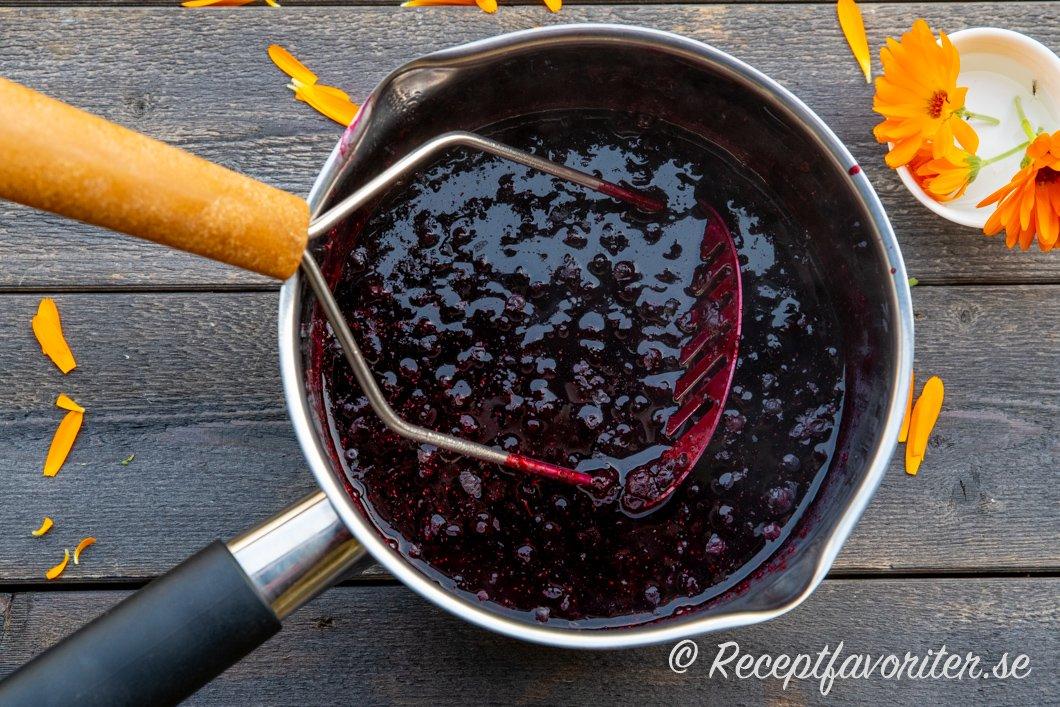 Bär eller frukt kokas och mosas i en kastrull.