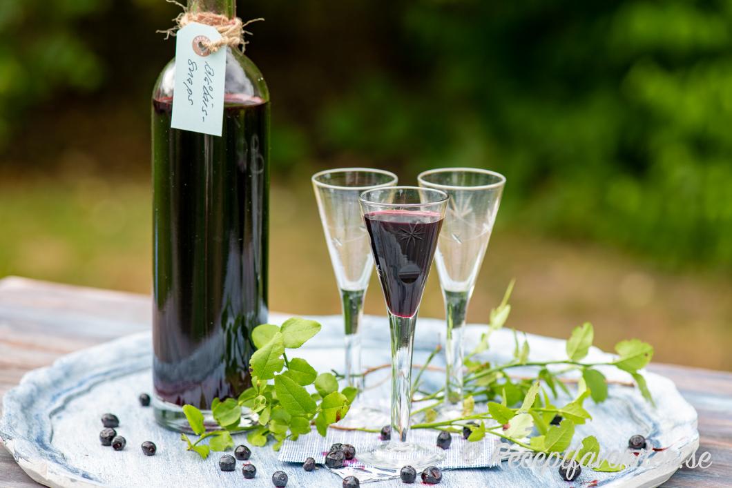 Blåbärssnaps serverad i snapsglas på bricka