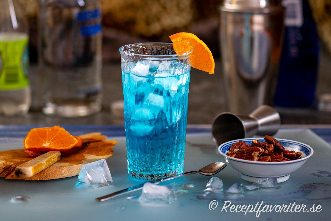 Drinken Isbjörn eller Blue Lagoon i highballglas med rostade pekannötter till.