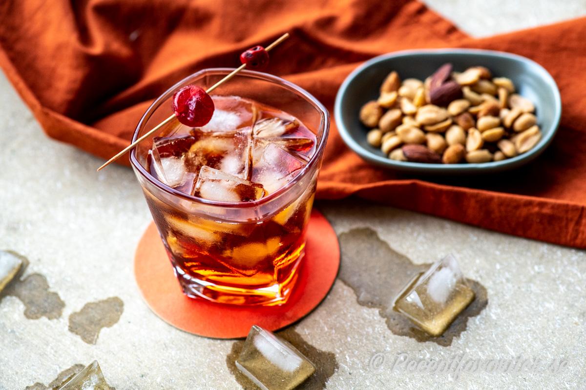 Boulevardier cocktail garnerad med ett rött cocktailbär.