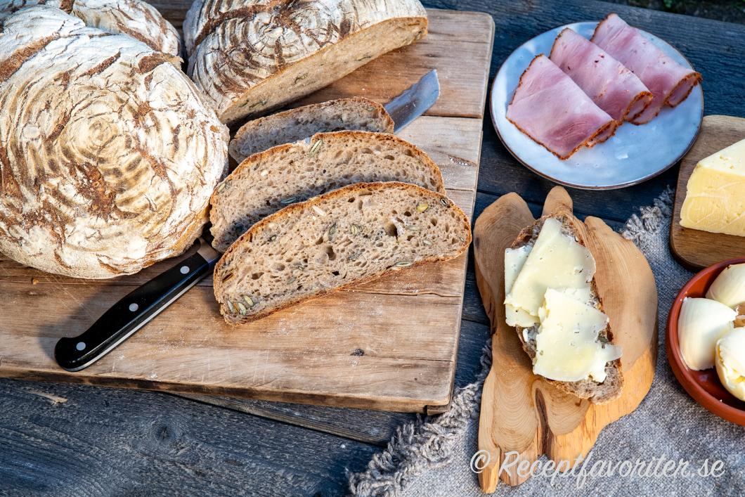 Surdegsbrödet serverat med smör, ost och skinka till fika, frukost eller mellanmål.