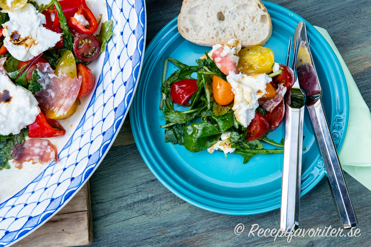 En sallad med italiensk stor mozzarella - burrata - salami, tomater, paprika och balsamvinäger.