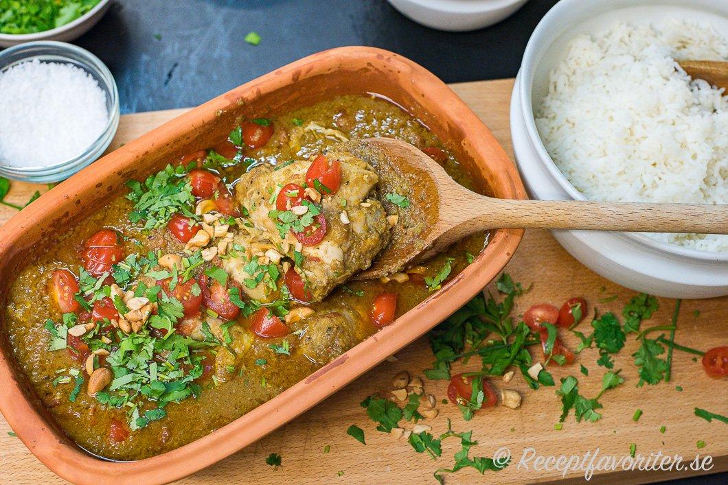 Smörig kycklinggryta serverad med basmatiris, färsk koriander, nötter och cocktailtomater.