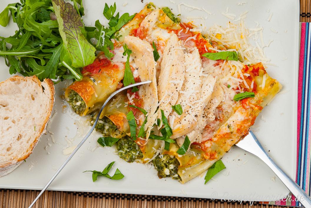 Cannelloni toppad med stekt kycklingfilé på tallrik med sallad och bröd till.