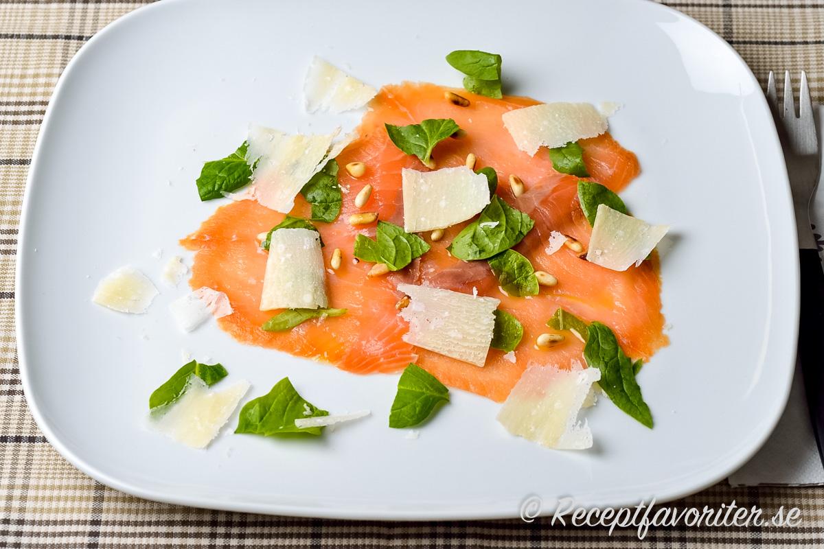 Carpaccio på lax i tunna skivor garnerad med rostade pinjenötter, hyvlad parmesan samt färsk basilika.