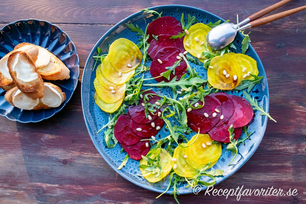 Röd- och gulbetscarpaccio serverat med getostbröd