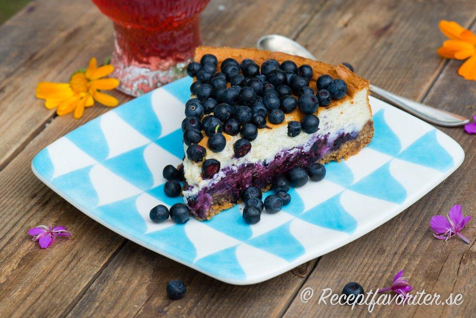 En bit bakad cheesecake med blåbär på tallrik