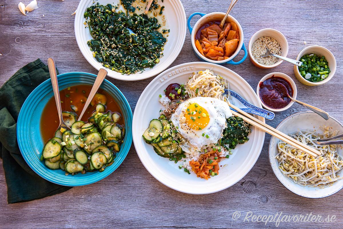 Den chilipicklad gurkan serverad till Bibimbap - koreansk rispytt samt tillbehör.