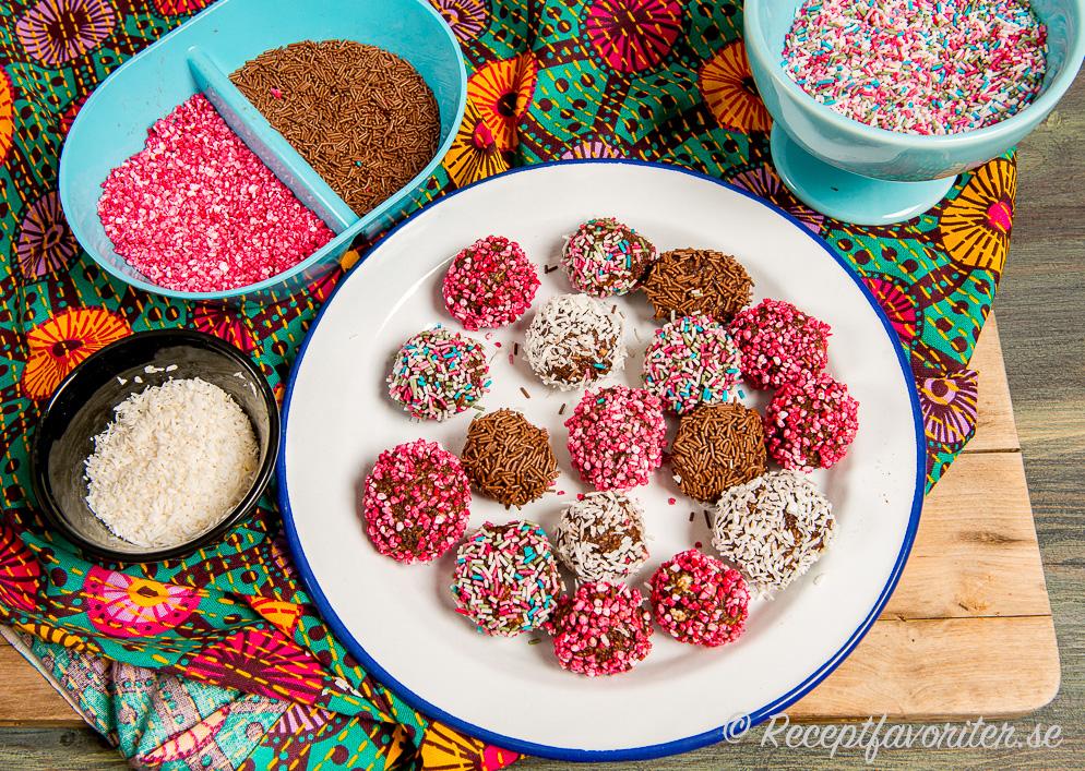 Chokladbollar med olika toppings i skålar.