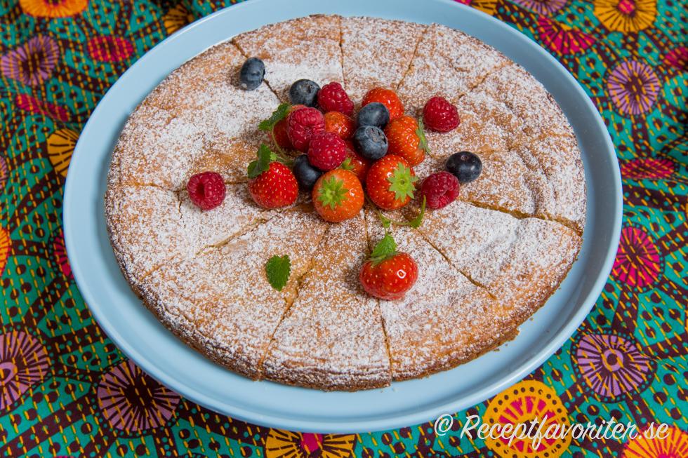 En kladdkaka med vit choklad garnerad med florsocker och färska jordgubbar, blåbär och hallon.