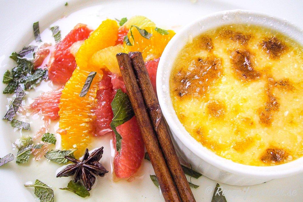 Crème brûlée med marinerad citrus på tallrik.