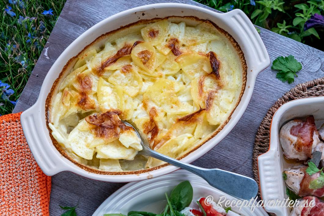 Potatisgratäng serverad som sås och tillbehör i ett