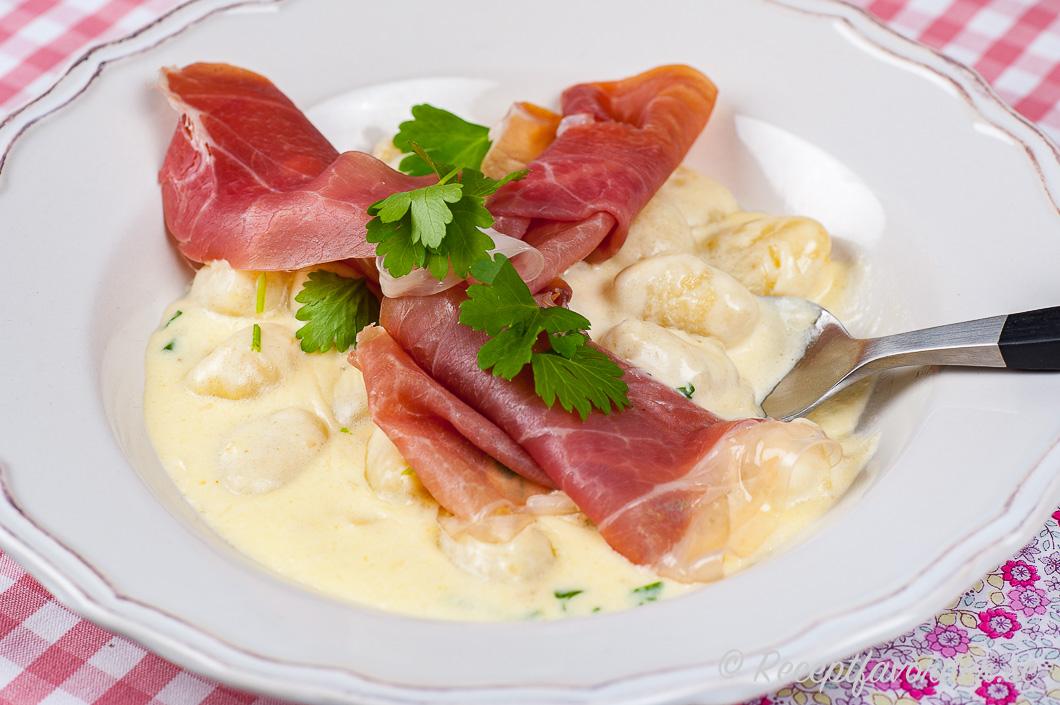 Toppa pastan eller gnocchin med några skivor lufttorkad skinka samt bladpersilja.