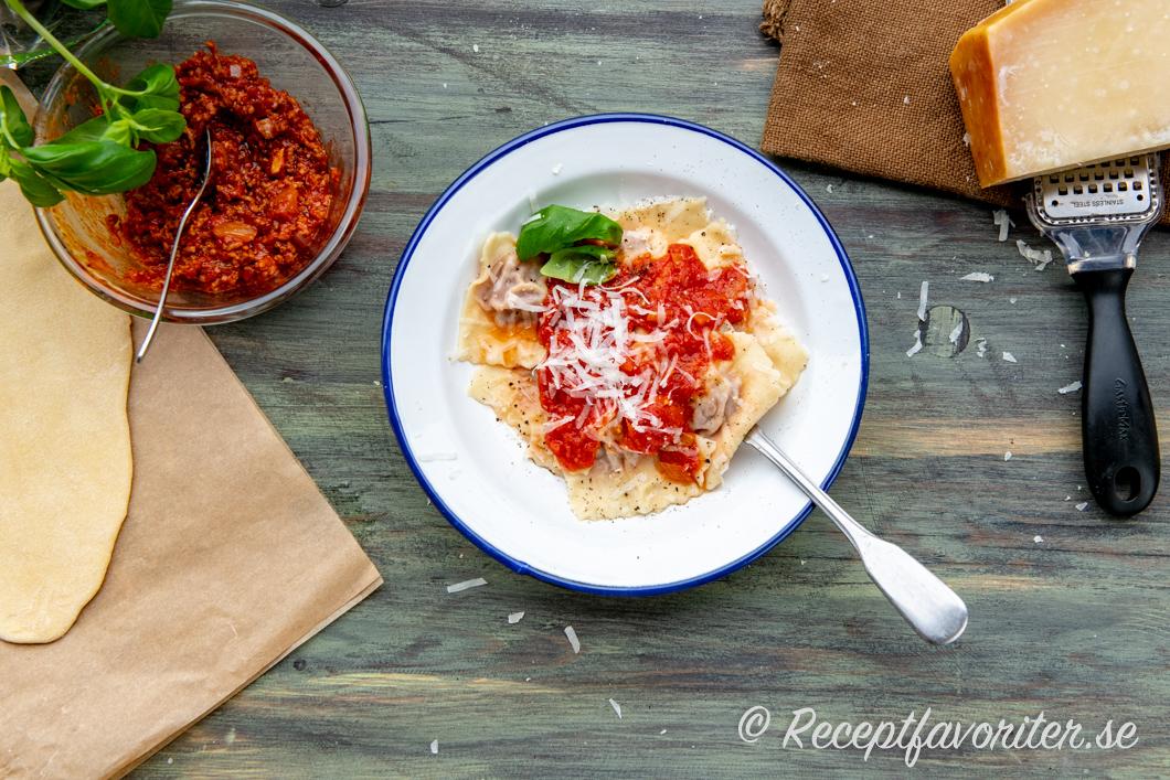 Raviolis med köttfärsfyllning serverade med tomatsås, parmesan och basilika