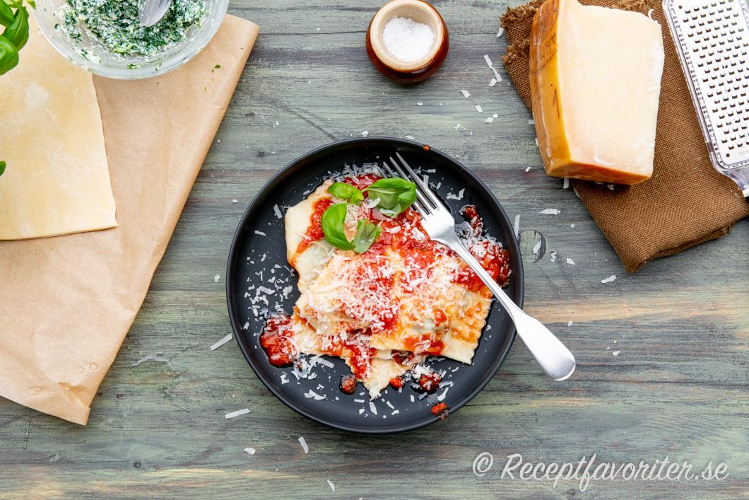 Raviolisar med spenat och ricottafyllning på tallrik med tomatsås och riven parmesan.