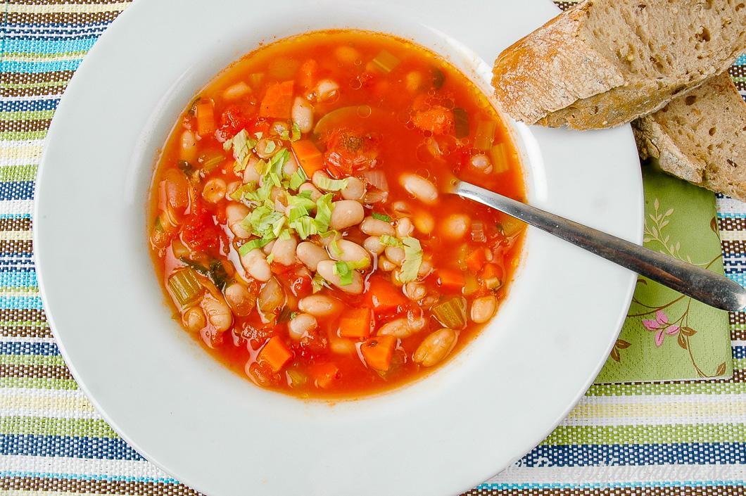 Mustig och god fasolada soppa med vita bönor och tomat i tallrik