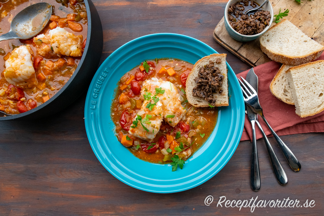 Italiensk tomatdoftande fiskgryta med lubb serverad med surdegslimpa och tapenade