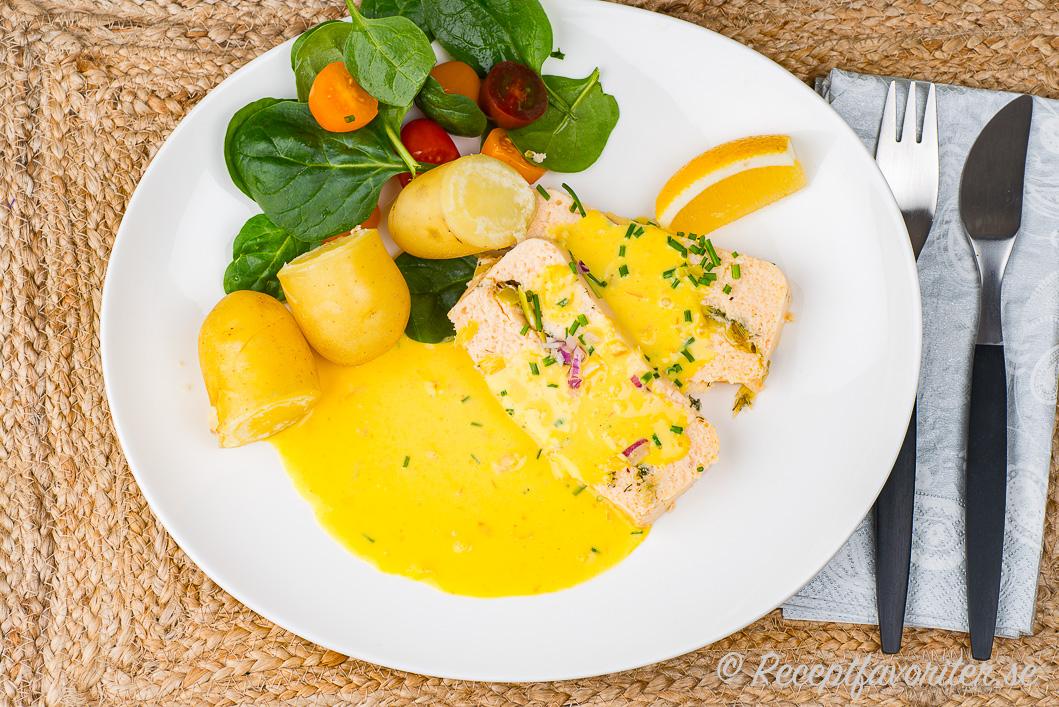 En tallrik fiskterrine i skivor med gul saffranssås, kokt Amandine delikatesspotatis, citronklyfta, babyspenat och cocktailtomater garnerad med hackad gräslök och rödlök.