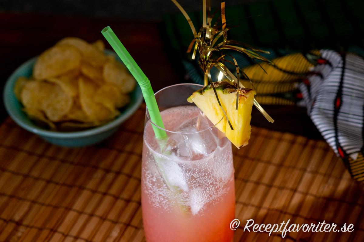 Flamingodrinken garnerad med en bit färsk ananas, sugrör och drinkpinne med glitter.