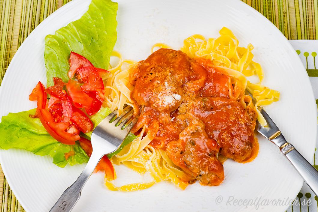 Fläskfilé i skivor lagad i tomatsås och toppad med parmesan på tallrik