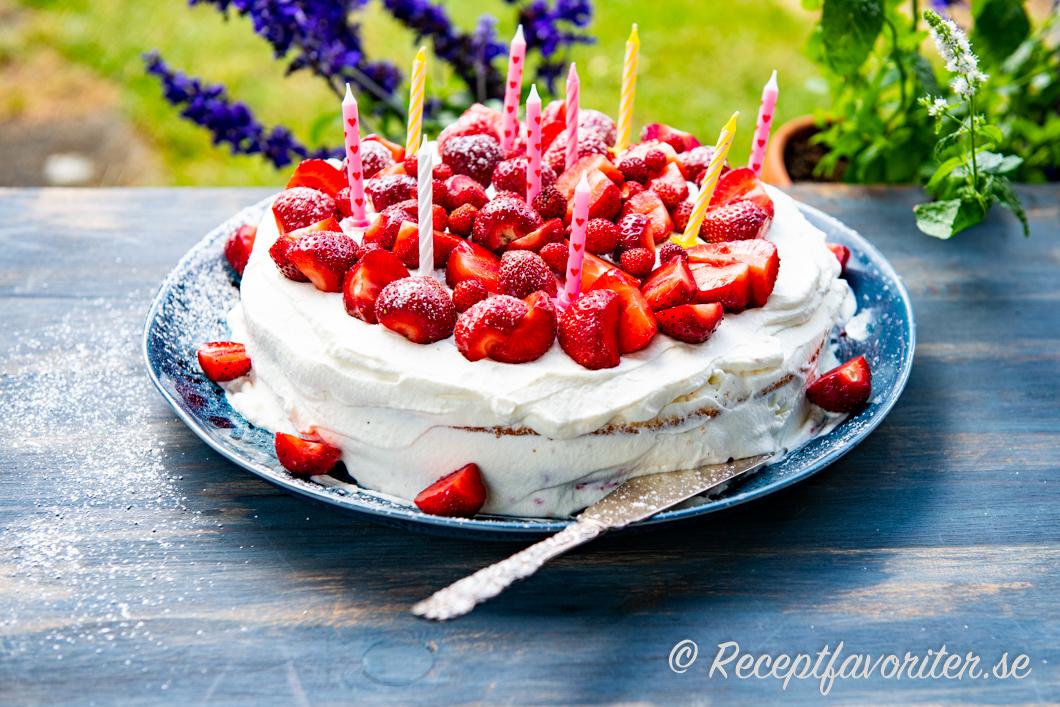 Födelsedagstårta med jordgubbar och ljus på fat