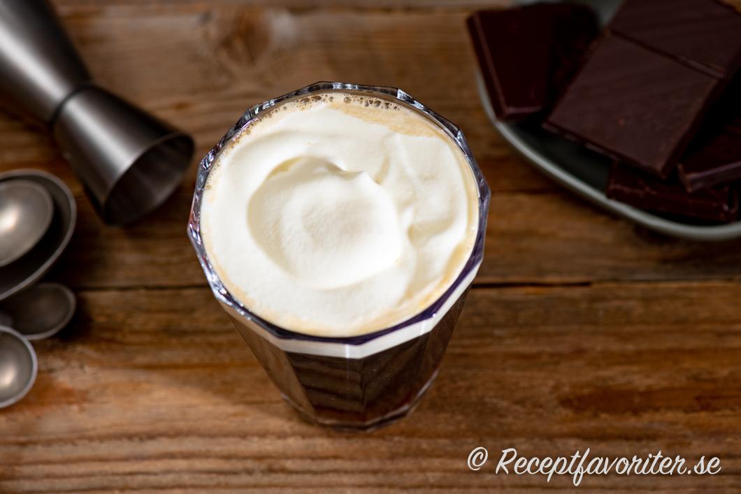 Franskt kaffe med konjak i glas toppat med lättvispad grädde