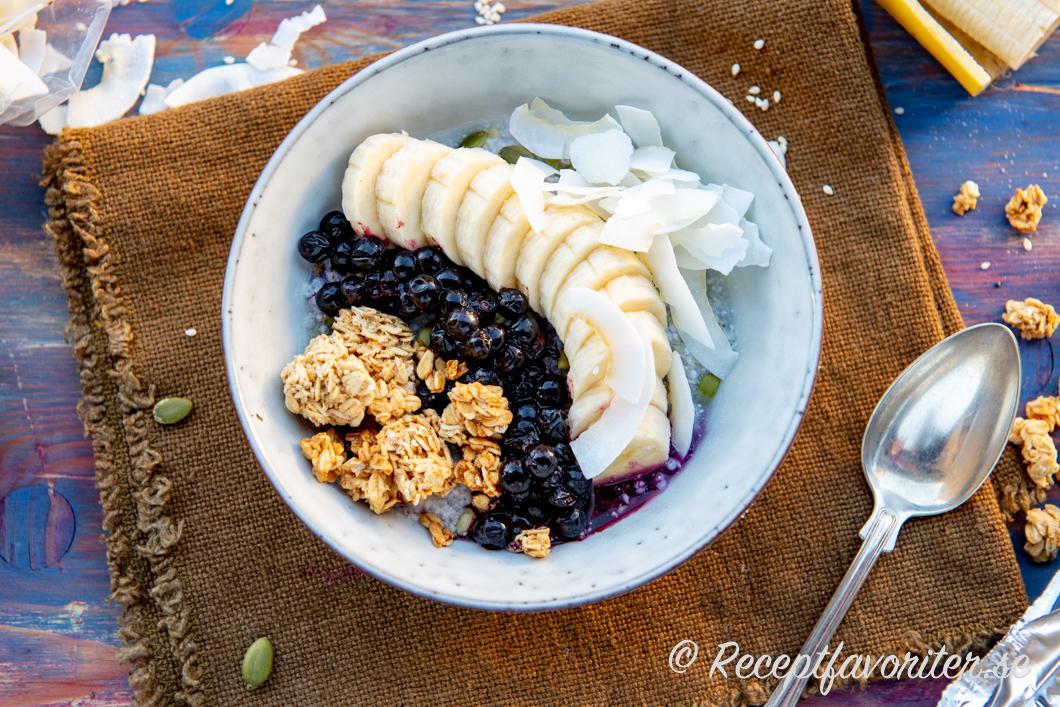 Toppa frögröten med det du gillar. Här med kokosflakes, rårörda blåbär, granola och skivad banan.