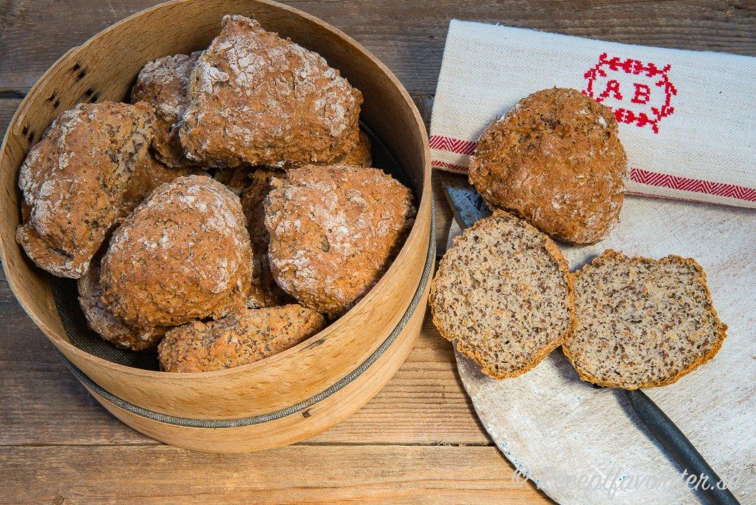 Nybakta gluten- och laktosfria frukostbullar i brödkorg samt uppskurna i halvor