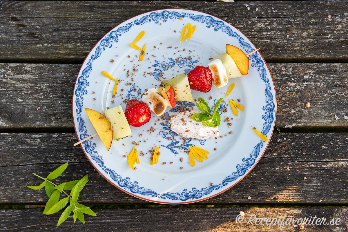 Ett fruktspett serverat med Daimgrädde, ringblomma, riven Daimchoklad, mynta samt citronverbena som garnering.