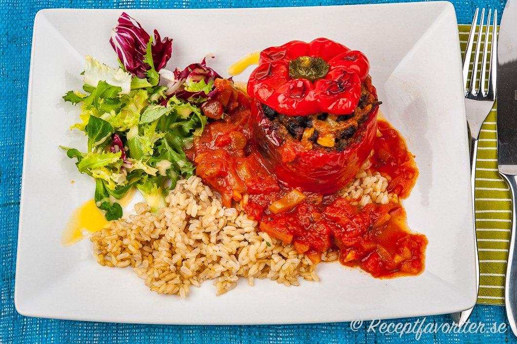 En fylld röd paprika serverad med förslag på tillbehör