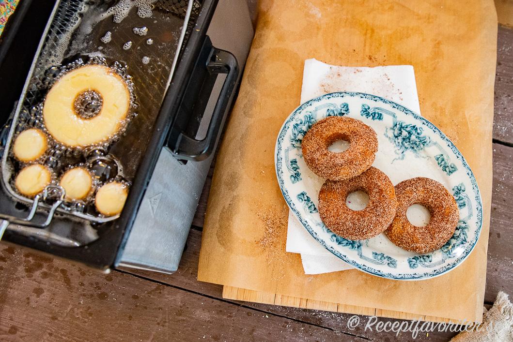 Glutenfria munkar eller doughnuts i fritös och nyfriterade på fat