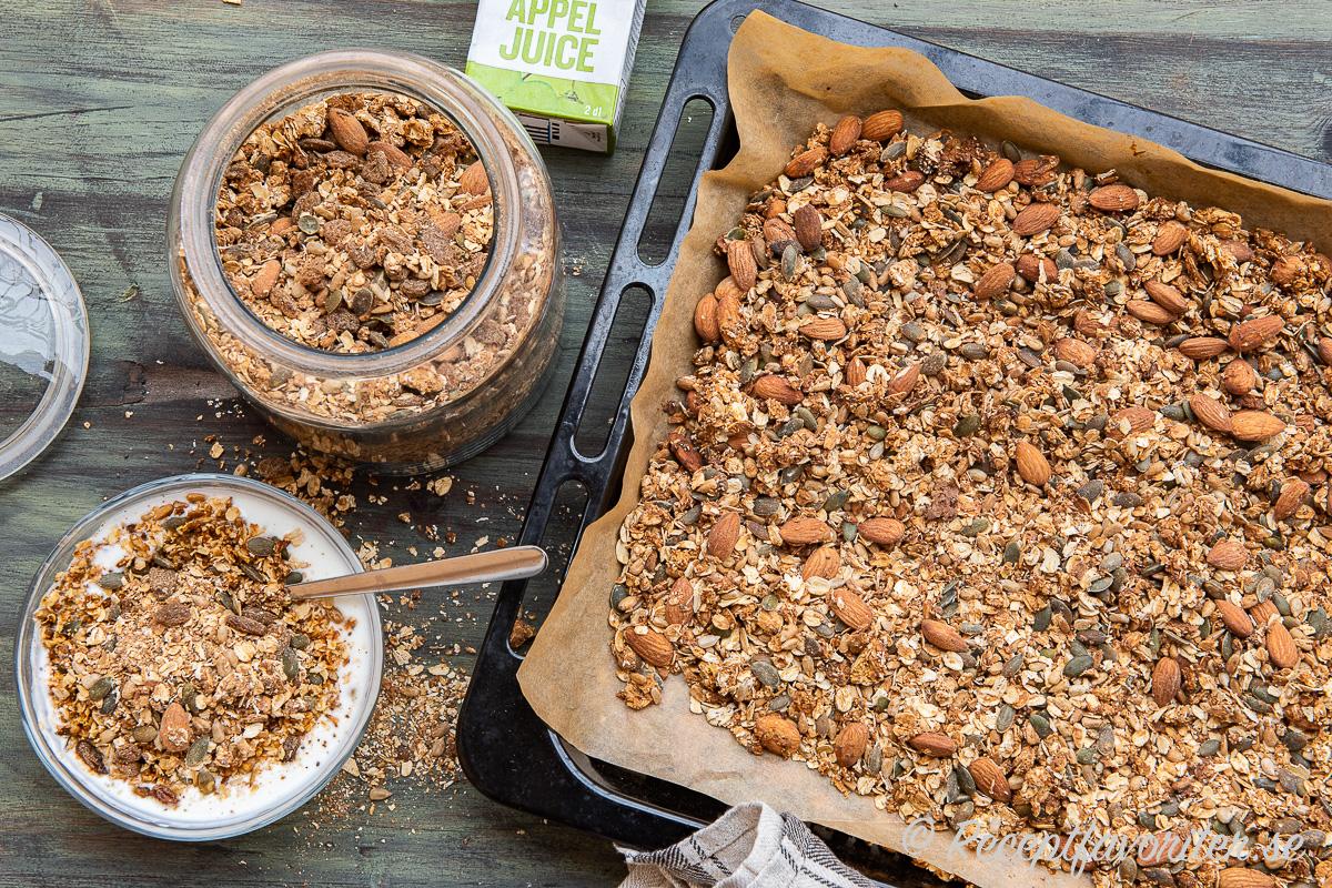Granola med äppeljuice i burk, i frukostskål samt på ugnsplåt.