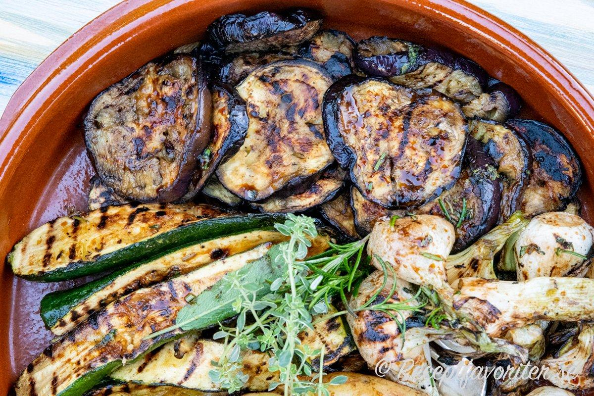 Grillade skivor av aubergine serverade som tillbehör med knipplök och zucchini