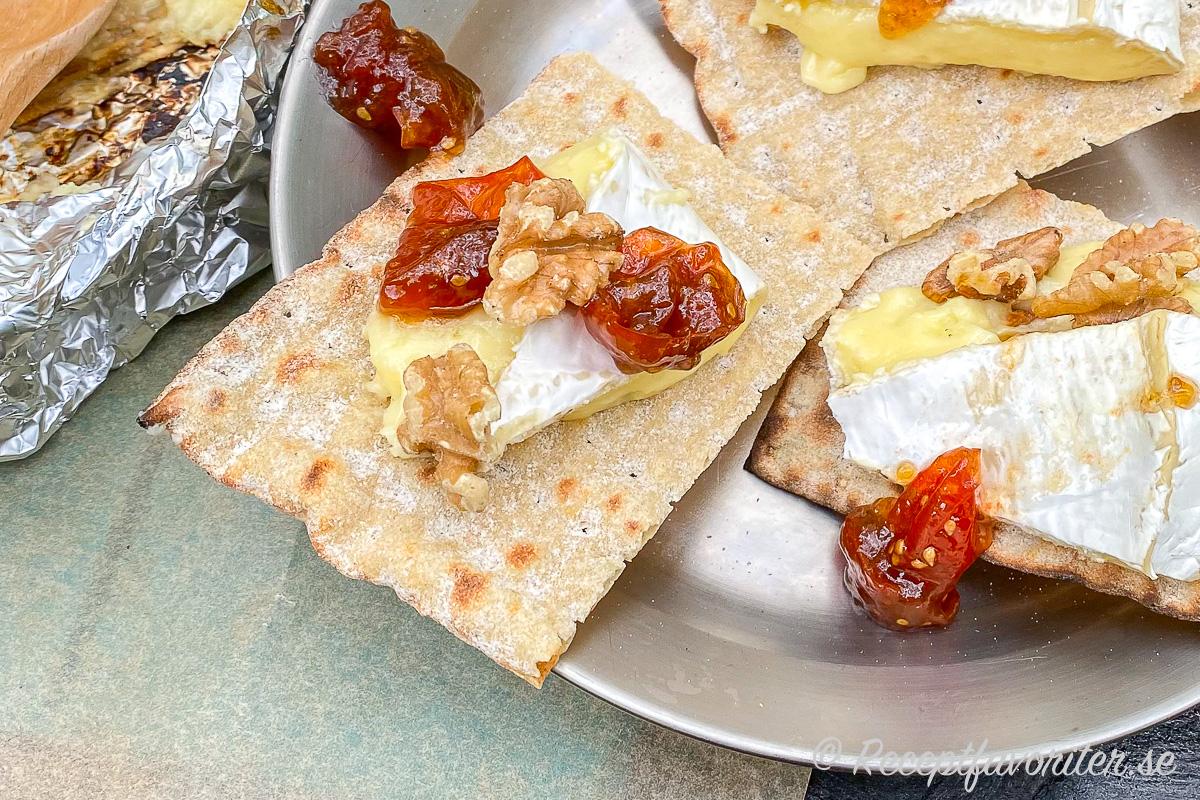 Grillad smält Brieost på knapriga tunnbröd med söt tomatmarmelad och rostade nötter. Enkelt och gott som tilltugg, förrätt eller osträtt vid grillen.