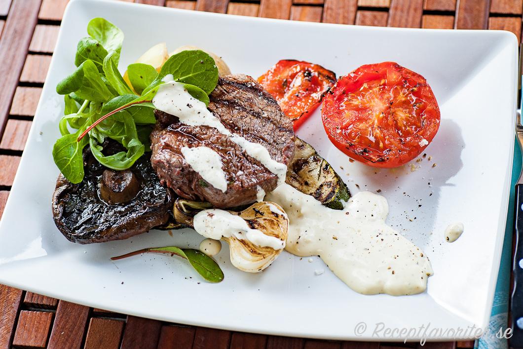Grilla en bit oxfilé och grönsaker som knipplök, zucchini samt tomathalva och servera med en krämig aioli-vitlökssås samt garnera med lite finbladig sallad.