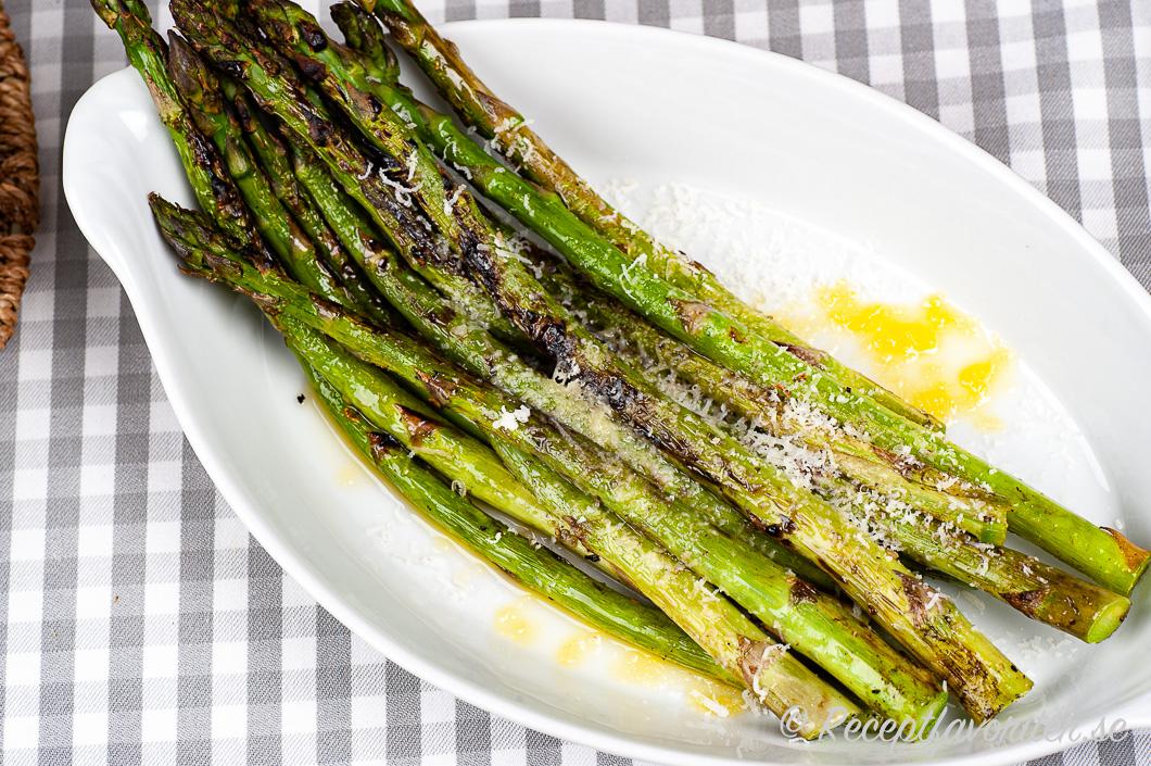 Grillad grön sparris på fat med riven parmesan och smör.