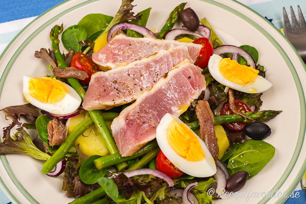 Grilade tonfisk i skivor på sallad med potatis, oliver, kokt ägg, gröna bönor, rödlök och vinägrett.