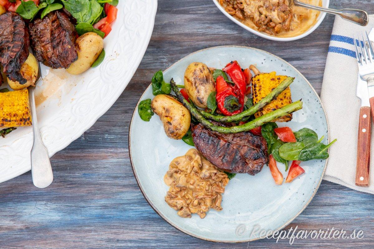 Vildsvinskarré serverad med tillbehör som kantarellsås, potatis och grillade grönsaker på tallrik.